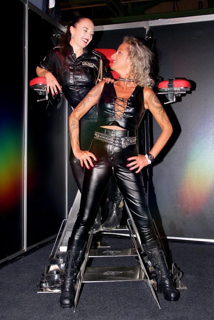 Lady Vivin und Amalie von Stein auf der Boundcon München 2019 am BDSM-Möbel Stand von Carat XXX.